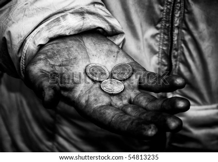 Dirty hands of a beggar with some coins