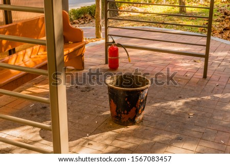 Dirty, littered public smoking area with wooden bench, ashcan, and fire extinguisher