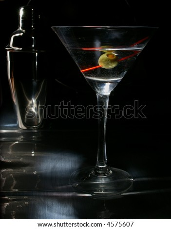 Dirty martini & shaker with dramatic lighting.