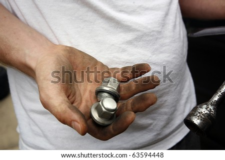 Dirty mechanic's hand with nuts
