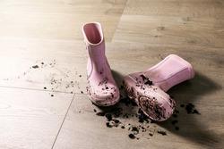 dirty muddy kids rubber rain boots on laminate floor