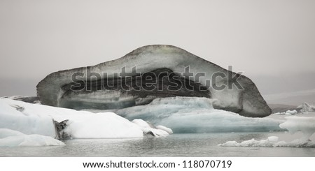 Dirty muddy melting iceberg floating in water
