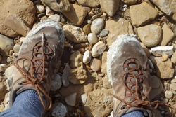 Dirty neutral brown shoes on sandy stone underground. Hiking in nature with tramping boots. Hip shoe style for outlaws.