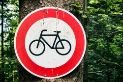 Dirty no Cycling red traffic warning sign with black bicycle mounted on tree in dark forest