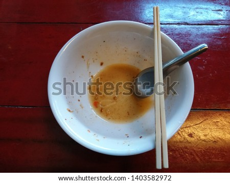 Dirty noodles bowl after meals with stainless soup spoon and plastic chopsticks on dark brown wooden table. Delicious until the last drop of soup. Delectable / Mouthwatering / Yummy.