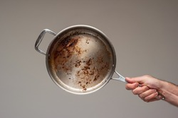Dirty oily burnt metal frying pan held in hand by male hand. .
