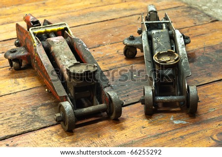 Dirty old car jack on wooden boards