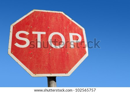 Dirty old red British Stop sign and blue sky.