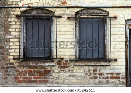 Dirty old window with bars on a grungy brick building.