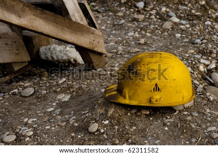 Dirty old work helmet left on the ground of construction site