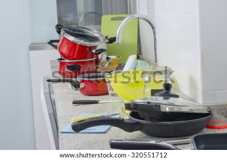 Dirty pan and pots in a messy kitchen in domestic household.