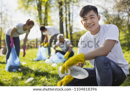 Dirty park. Positive male volunteer grinning to camera while collecting litter