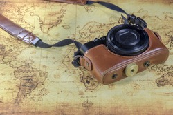 dirty pocket compact camera on a old world map