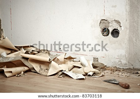 dirty room with wallpaper on the ground