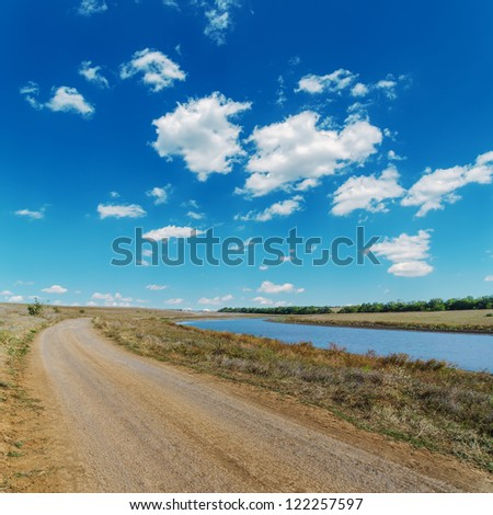 dirty rural road near river and blue sky