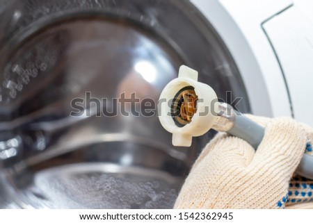 Dirty rusty filter of water supply hose of washing machine close up needed to be cleaned to prevent damage or leak.