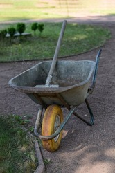 dirty rusty wheelbarrow with a shovel inside, left by a worker, stands in the garden