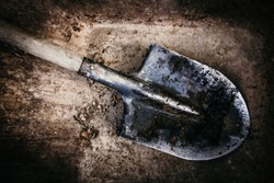 Dirty shovel in fresh soil. Deep hole in the ground. Rusty old tool on construction. Dig deep ditches and pits.
