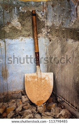 Dirty shovel in the corner of a rough unfinished  concrete wall