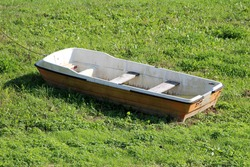 Dirty small plastic river boat with wooden board seats partially filled with rainwater left on side of uncut grass covered river bank and secured with rusted chain