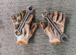 Dirty smeared gloves and metal spanners lie on the background. Industrial parts and accessories for workers. Photography, concept, copy space.
