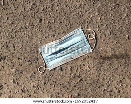 Dirty surgical or medical mask with rubber ear straps on the ground. Typical 3-ply doctor mask to cover the mouth and nose. Used procedure mask from bacteria. Ecology waste concept. Stock photo
