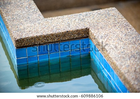 Dirty swimming pool water and pool edge