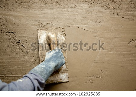 dirty trowel with glove hand plastering cement mortar in the wall