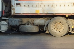dirty wheel of a big truck on a gray asphalt in the street