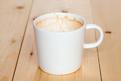 Dirty white mug of coffee lying on the boards