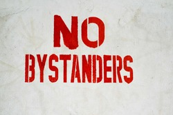 Dirty white painted wall with a bold NO BYSTANDERS sign in red paint