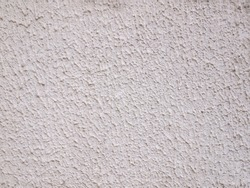 Dirty white rough surface. Granular plaster. An uneven pattern on the wall.