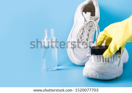 Dirty white sneakers with brush and special tool for cleaning them on blue background. Hand in protective gloves. protective gloves. Washing concept. Regular care about sneakers. Space for text.