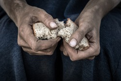 dirty women's hands with a piece of bread, poverty, hunger