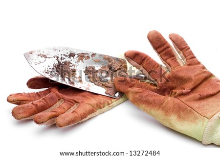 Dirty worn gardening gloves with a garden spade