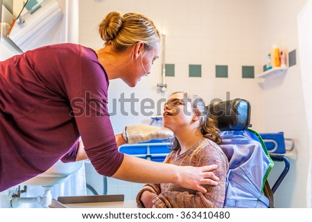 Disability a disabled child being cared for / Disability a disabled child in a wheelchair being cared for with help from a nurse