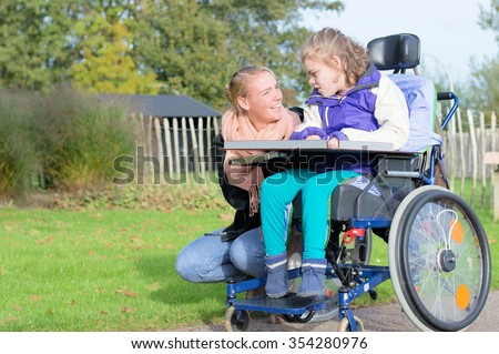 Disability a disabled child in a wheelchair relaxing outside together with a carer / Disability a disabled child in a wheelchair relaxing outside