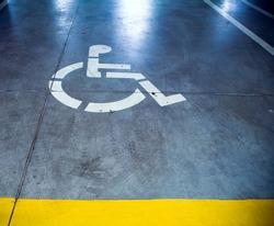 Disability sign in parking garage, underground interior