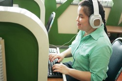 Disability young blind person happy woman in headphone typing on computer keyboard working in creative workplace office.
