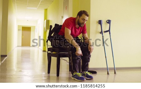 Disable man in the robotic exoskeleton sitting on the bench and taking off exoskeleton