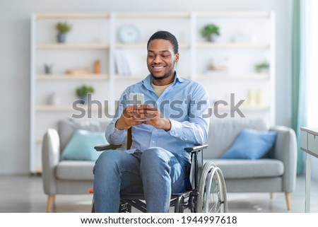 Disabled black man in wheelchair using smartphone, browsing web or watching movie at home. Handicapped young guy checking social media, speaking to friend on mobile device