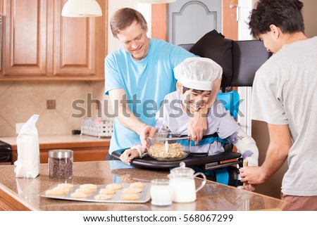 Disabled boy standing in stander, laughing as he makes chocolate chip chip cookies with father and brother in kitchen