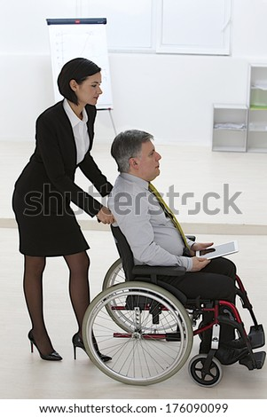 Disabled businessman in a wheelchair, pushed by a female partner
