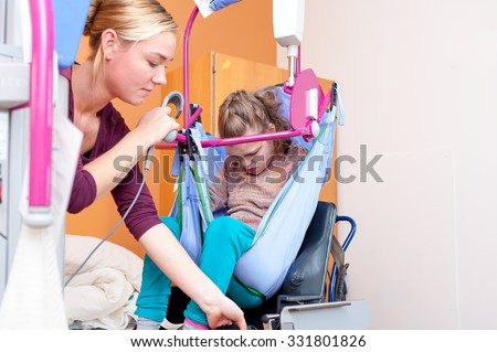 Disabled child being lifted into wheelchair using special needs equipment / Working with disability