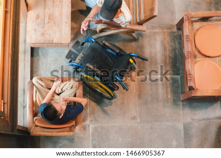 Disabled child on wheelchair and his dad spend the holidays doing indoor activities with fun, They sit in a coffee shop, Life in the education age of special Children, Happy disabled kid concept.