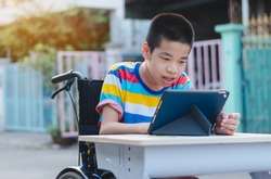 Disabled child on wheelchair happy time to use a tablet in the house with nature sun light, Special children's lifestyle, Life in the education age of special need kid, Happy disability boy concept.