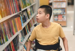 Disabled child on wheelchair having fun choosing books from shelves, Special children's lifestyle, Life in the education age of special need kids, Happy disability kid concept, Selective focus.