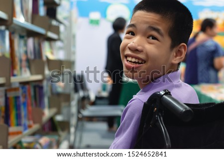 Disabled child on wheelchair trying begged parents to buy a book for him in books and toys fair,Special children lifestyle,Life in the education age of special need kids,Happy disability kid concept. Foto stock ©