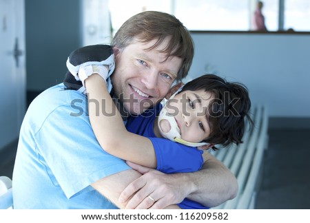 Disabled five year old boy giving father a big hug