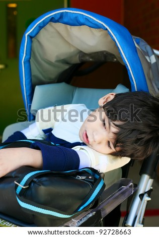 Disabled five year old boy in wheelchair at school, looking tired